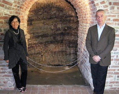 Giovanna Rizzolio and Italo Sobrino (proprietors) at the cut-out in their cellar that shows the striations of their terroir.