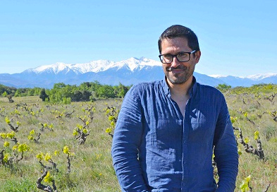 Anthony Guix standing among his old vines.